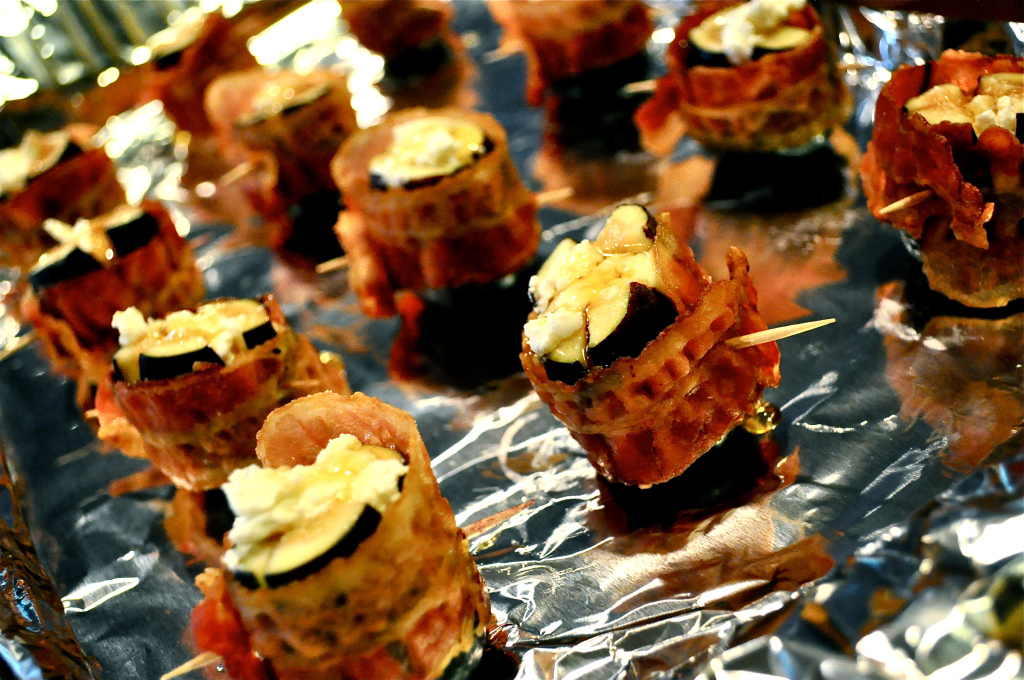 multiple figs stuffed with goat cheese and wrapped in bacon on a foil lined baking sheet
