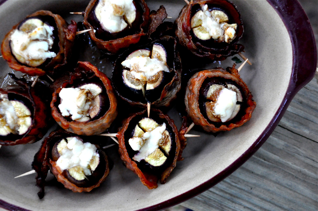 overhead view of a bowl of figs stuffed with goat cheese and wrapped in bacon