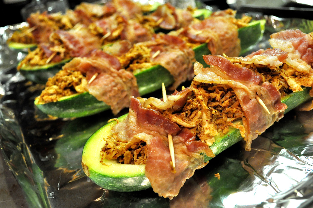 bacon wrapped stuffed zucchinis on a foil lined baking sheet