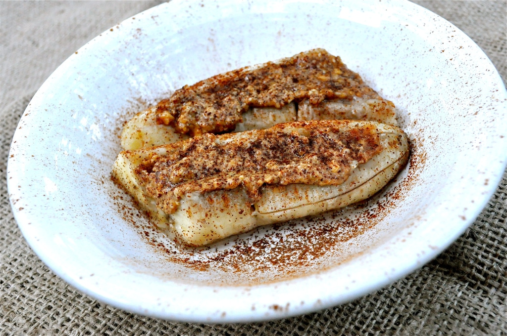 baked bananas in a white bowl topped with almond butter
