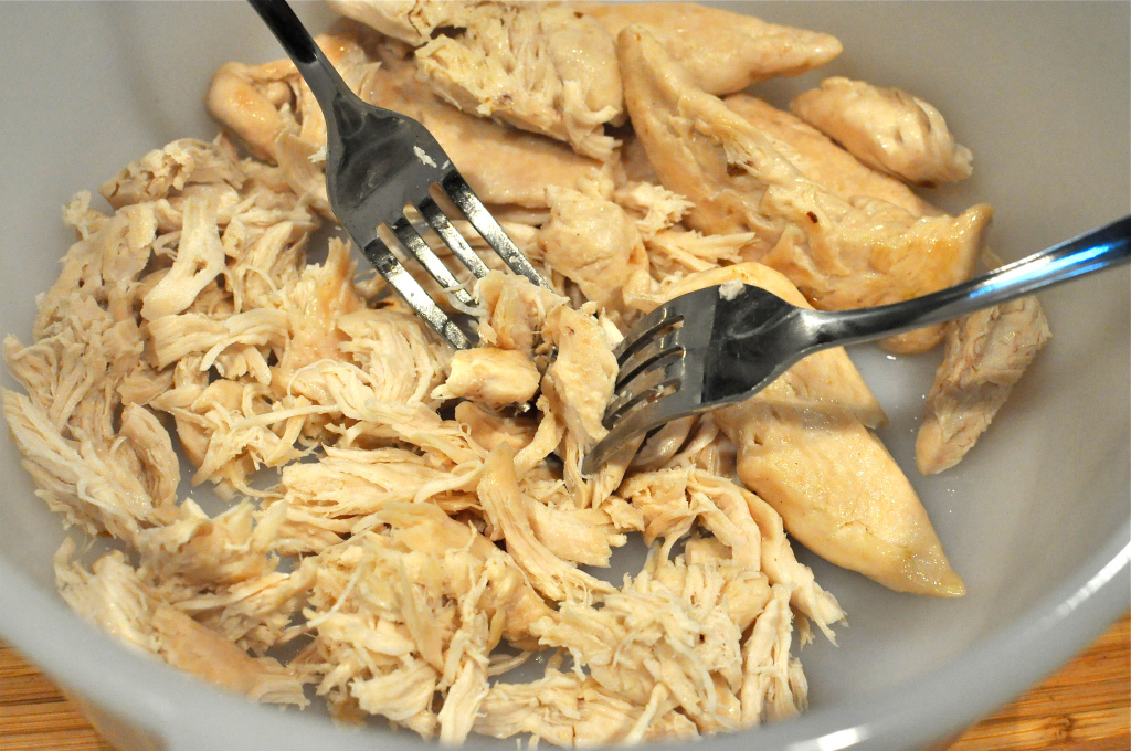 Chicken being shredded with two forks for Paleo Stuffed Avocados with Cilantro Lime Cream Sauce