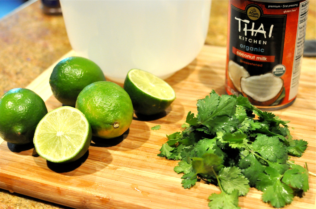 Coconut, limes, and avocados on a cutting board for Paleo Stuffed Avocados with Cilantro Lime Cream Sauce