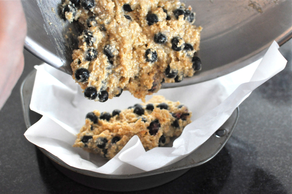 Paleo Blueberry scone batter being added to a round cake pan