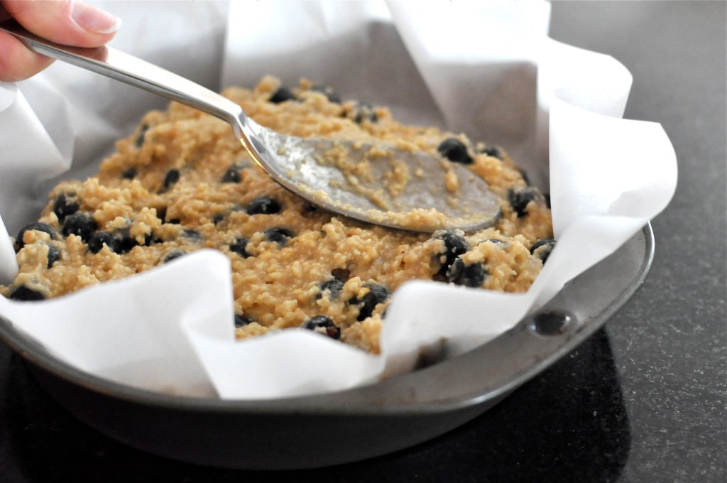 Paleo blueberry scone batter being smoothed into a cake pan