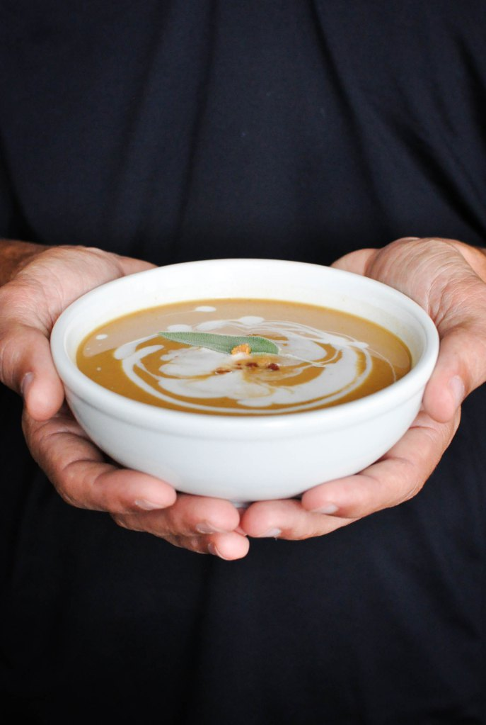 hands holding a bowl of Creamy Paleo Bacon Pumpkin Soup