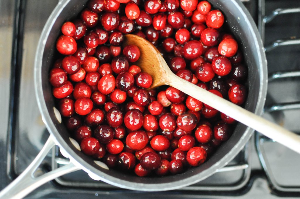 grey saucepan filled with cranberries on a stovetop with a wooden spoon in it