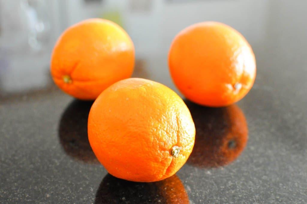 three oranges on a black granite countertop