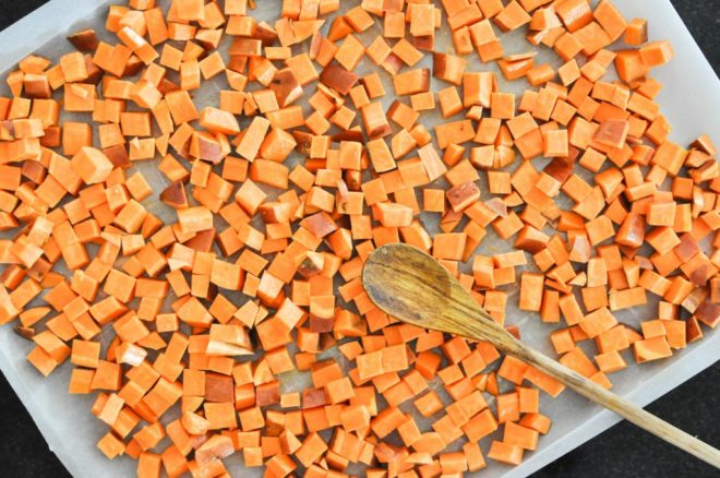 diced sweet potatoes on a baking sheet lined with parchment paper with a wooden spatula on top
