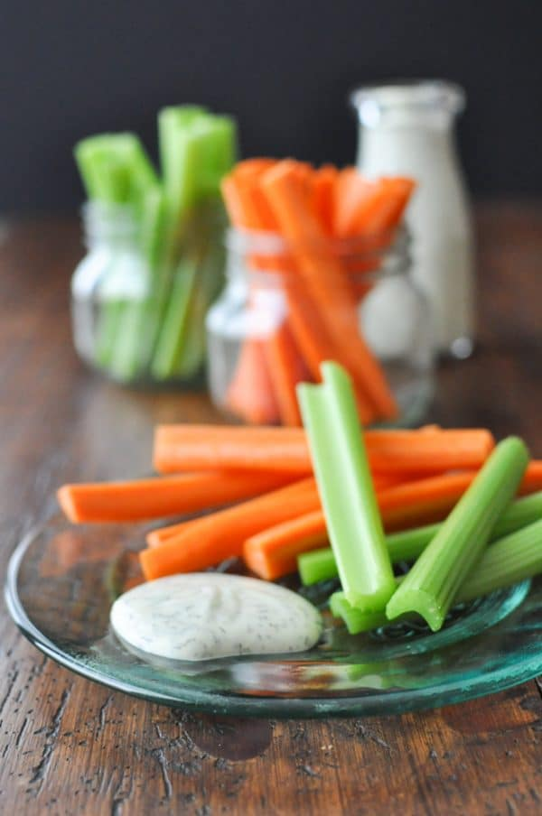 a green glass plates sits on a wooden table with celery and carrot sticks and a dollop of ranchos it with more celery and carrot sticks and ranch in jars blurred in the background