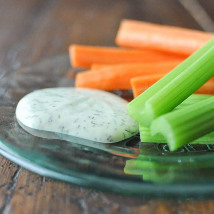 slices of green celery and orange carrots on a green glass plate with a dollop of paleo ranch