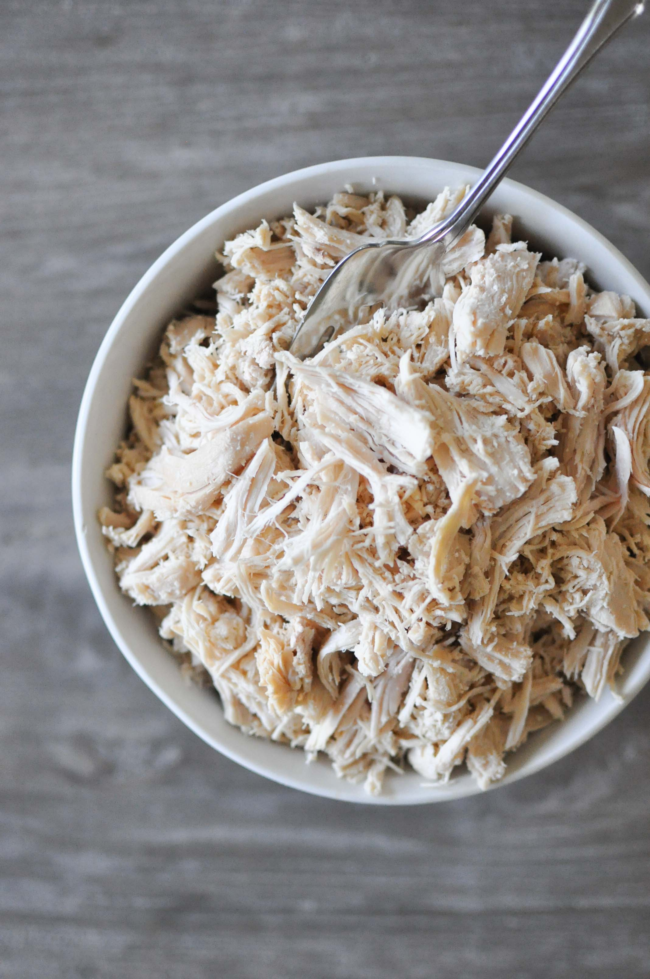overhead view of a white bowl on a grey wooden table filled with cooked shredded chicken