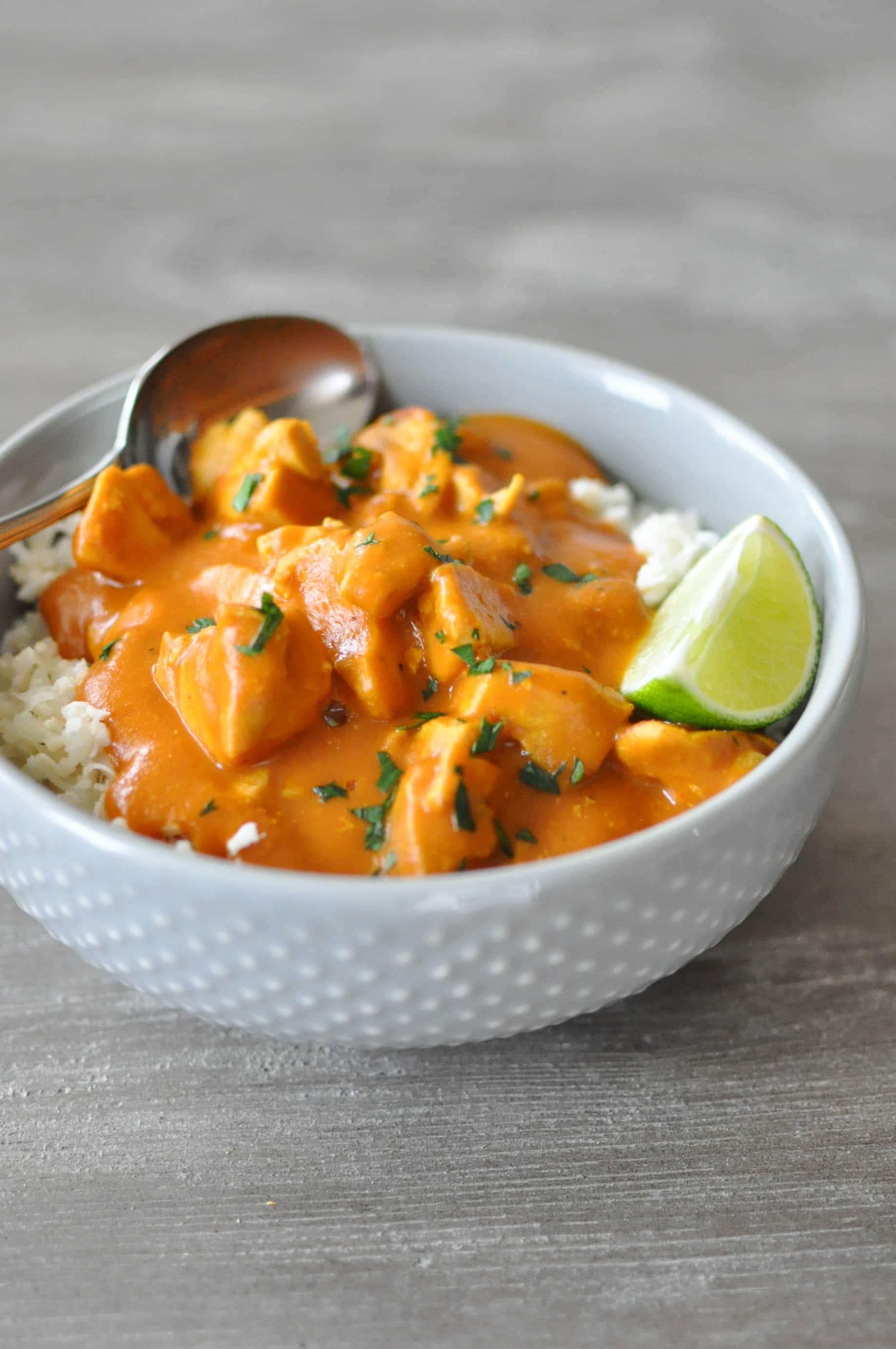 Paleo Pumpkin Curry over cauliflower rice in a grey bowl with a lime wedge on a wooden surface