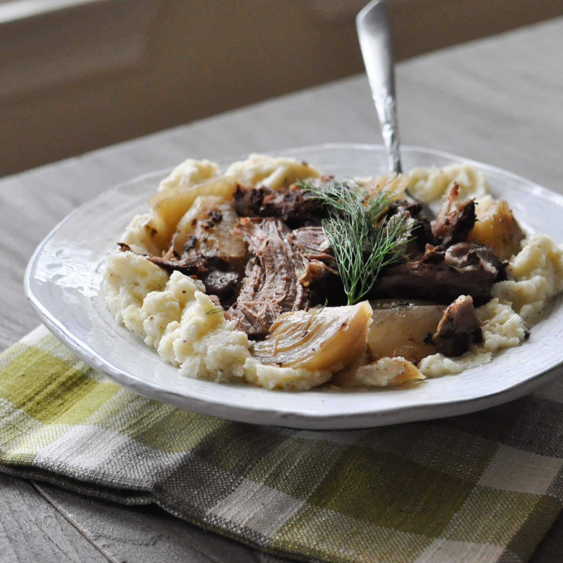a white plate of Cinnamon and Fennel Braised Pork with a neutral plaid napkin on a grey wooden table