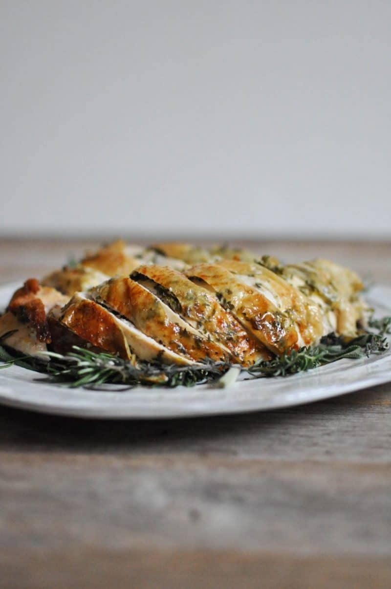 side view of sliced turkey breast with skin on a bed of herbs on a white plate on a wooden surface