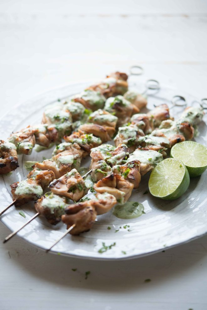 skewers of Citrus Chicken with Cilantro Garlic Sauce on a white plate