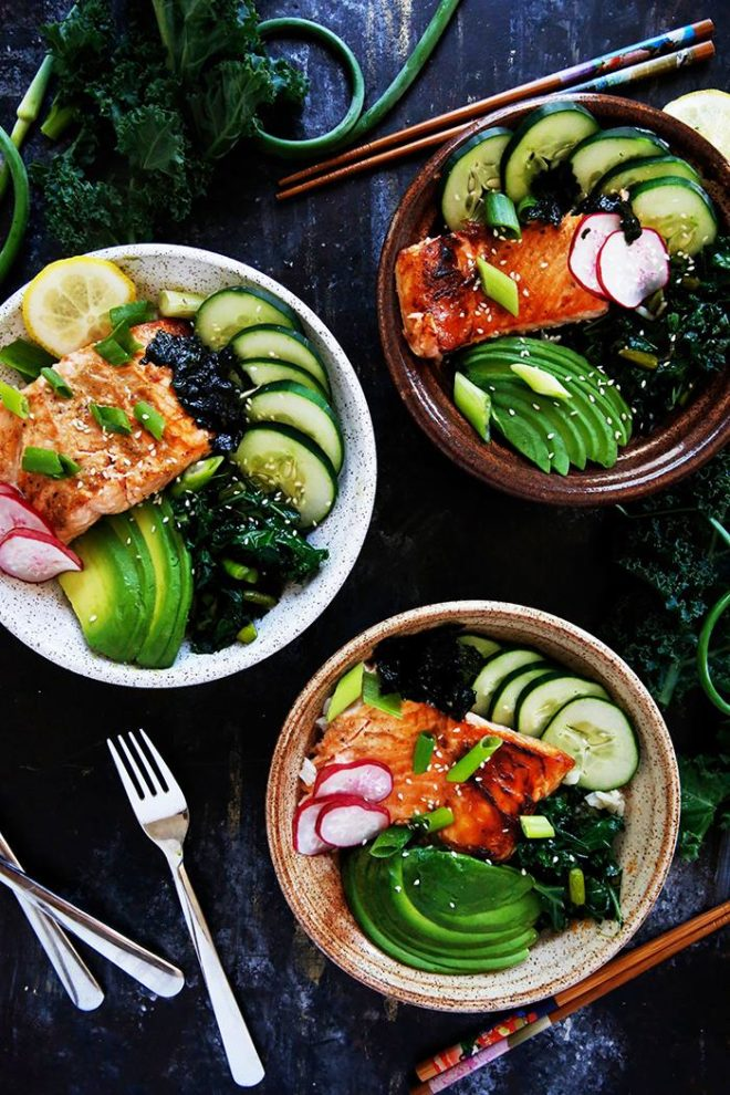 three grilled fish bowls with garlic scapes and kale