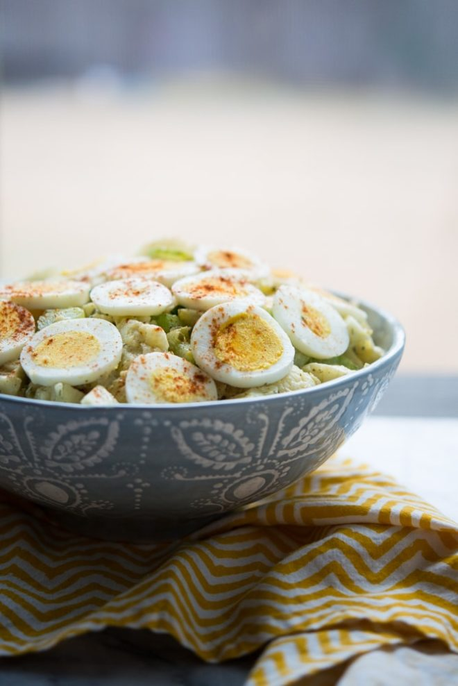 "bowl of Cauliflower ""Potato"" Salad with zig zag yellow napkin on a marble tabletop"