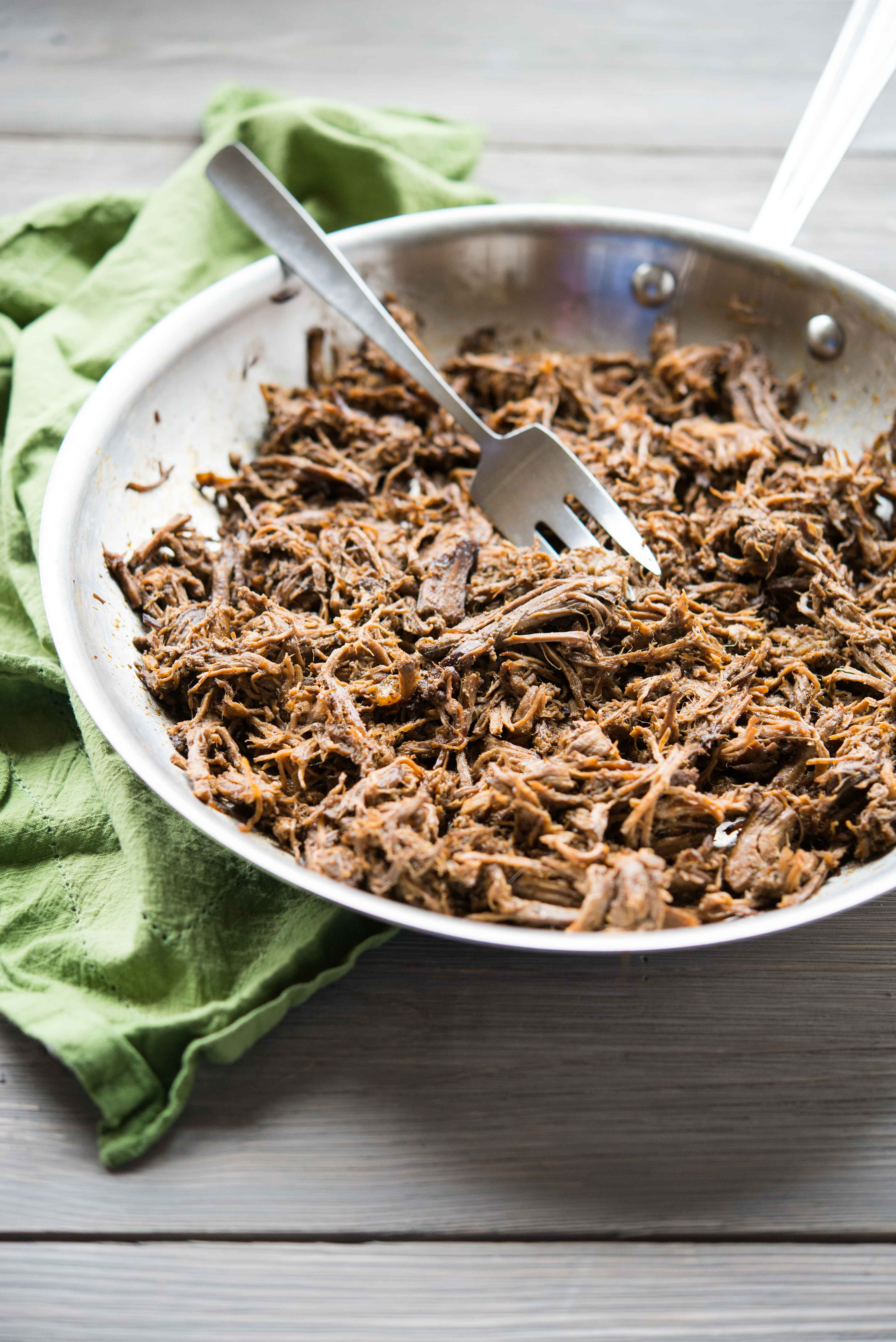 shredded beef barbacoa in a stainless steel pan on a wooden surface with a green towel - slow cooker freezer meals