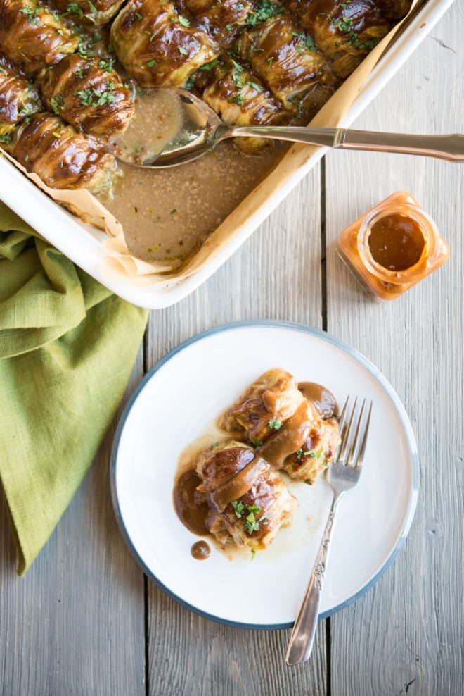 a white casserole dish filled with asian cabbage rolls and garnished with chopped cilantro and a white plate with two cabbage rolls on it sitting on a gray wooden table