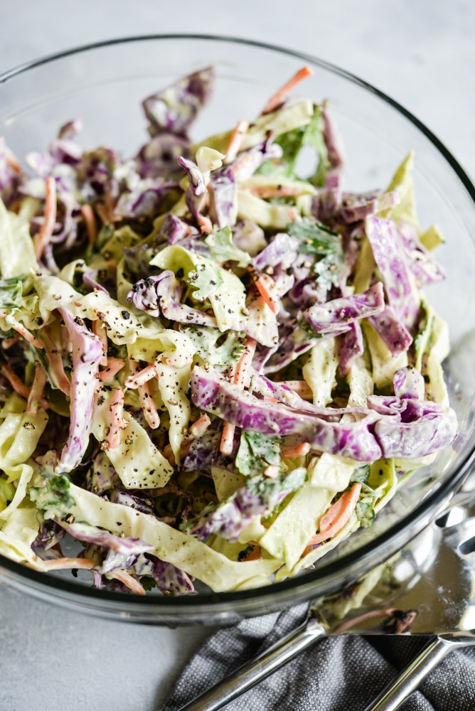 Mexican coleslaw with red and green cabbage and cracked black pepper in a glass bowl on a grey surface