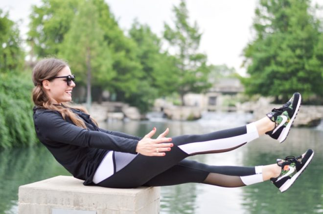 a woman in a fitness outfit doing an abdominal exercise in front of a river