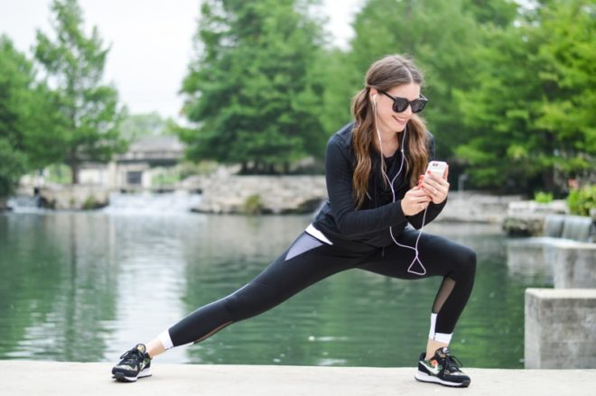 a woman in a fitness outfit in front of a river checking her phone