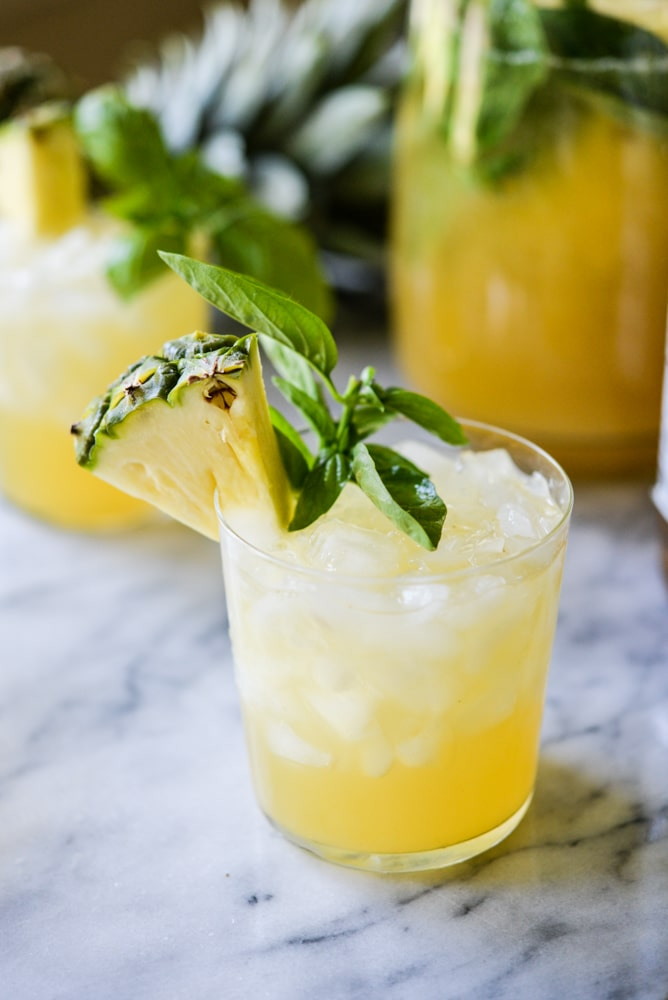 pineapple sangria in a glass with basil leaves as garnish on a marble surface