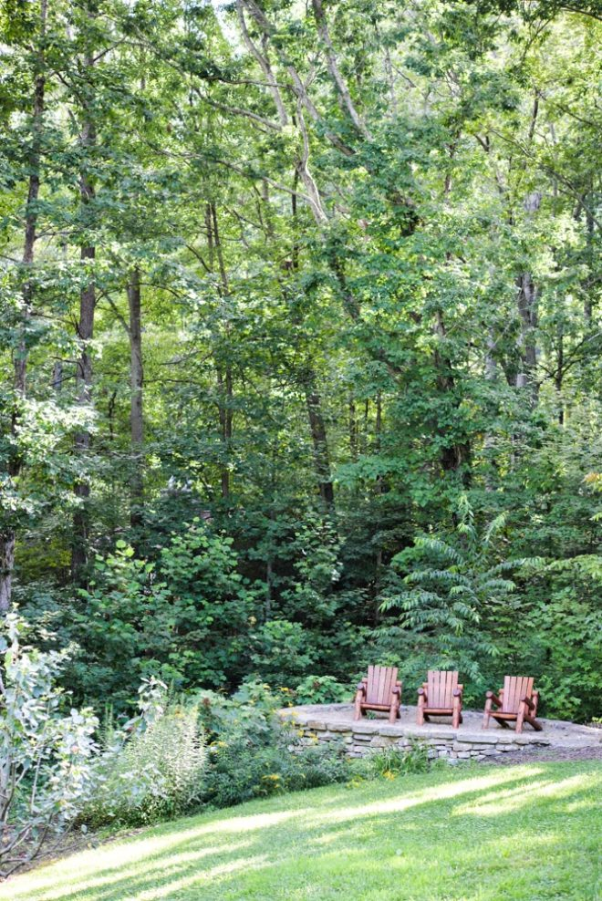 green trees and three Adirondack chairs