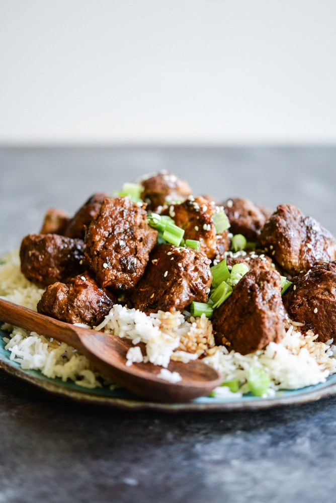 turkey teriyaki meatballs on a bed of rice on a blue plate with a wooden serving spoon