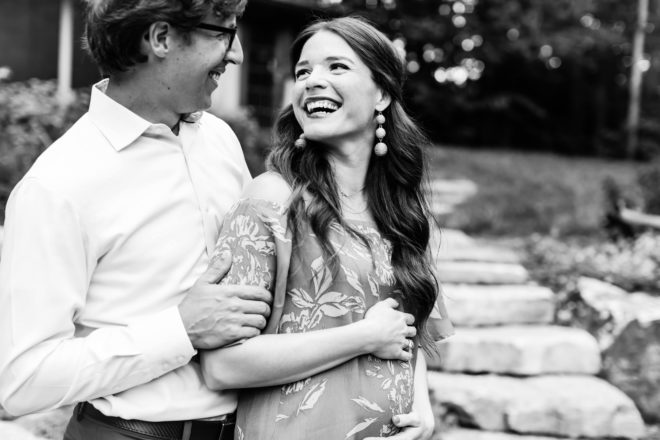 black and white photo of a man in a white button down collared shirt in black glasses holding his long dark haired white who is looking back at him and smiling while cradling her pregnant belly