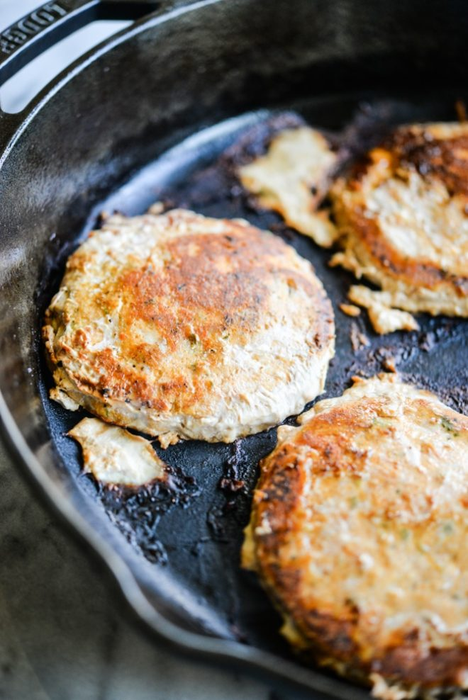 frozen tribali chipotle chicken patties in a cast iron skillet being cooked