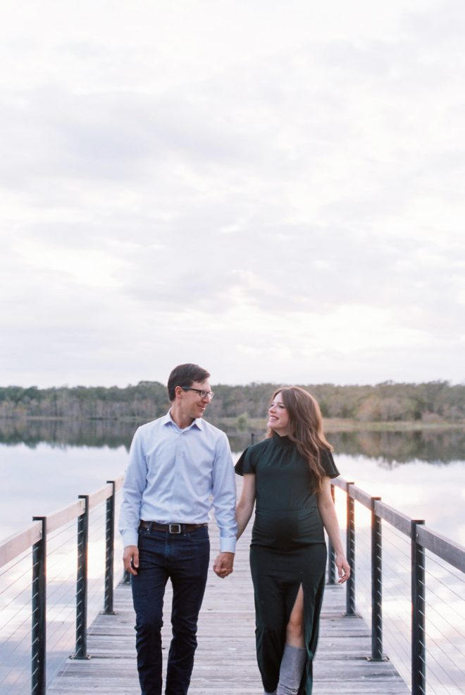 a man in a light blue shirt and blue jeans with black glasses and a pregnant woman with long dark hair in a green dress hold hands and walk along a pier that overlooks a still lake