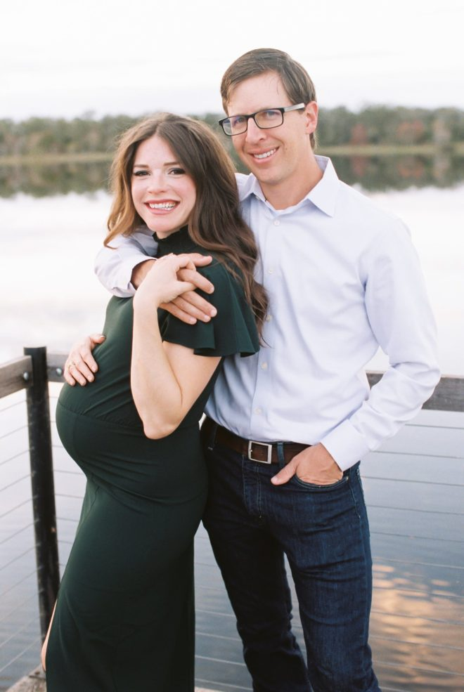 a man in a light blue collared button up shirt and blue jeans with black glasses has his arm around a smiling pregnant woman with long dark hair and a green dress on