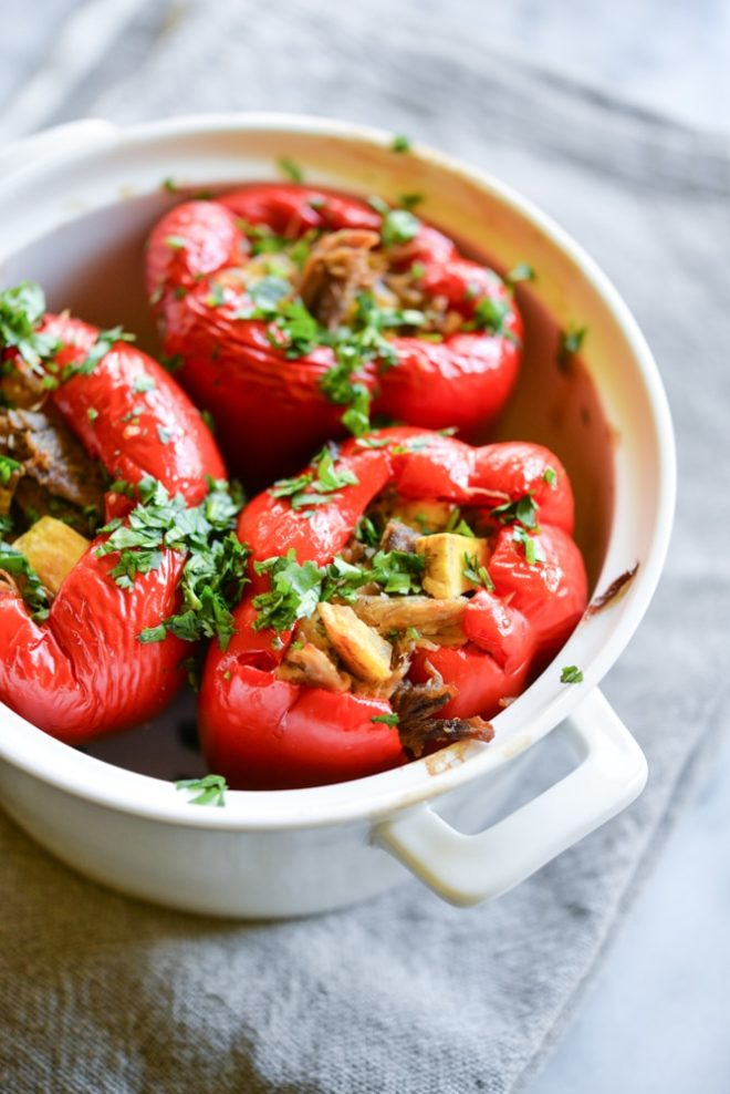 meal prep carnitas stuffed red bell peppers in a white casserole dish