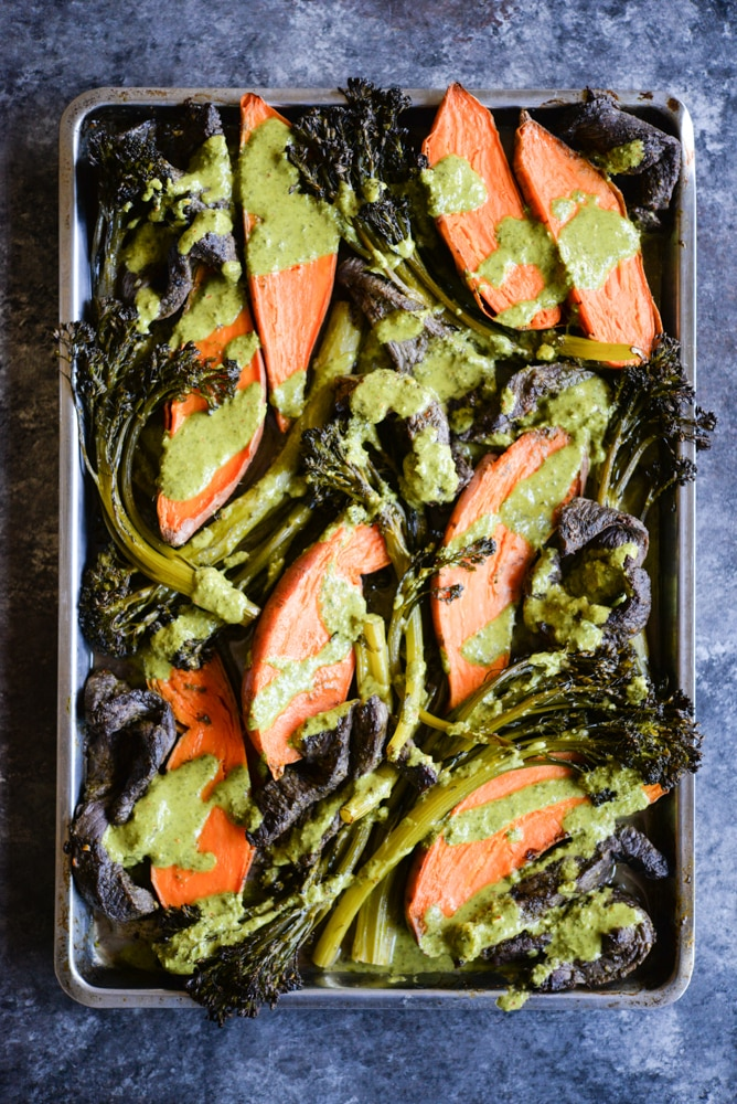 chimichurri beef sheet pan dinner with strips of steak, sweet potatoes, broccolini, and a bright chimichurri sauce