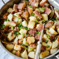 red potatoes, green onions, and crispy bacon in a stainless steel skillet with a large silver serving spoon on a marble surface