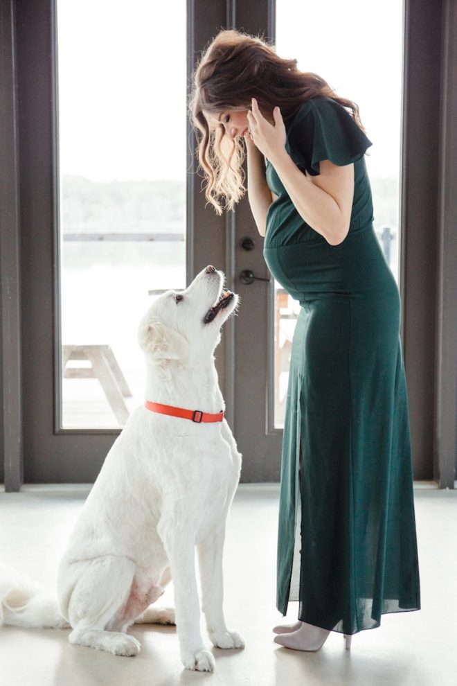 a long dark haired pregnant woman in a long green dress holds her hair back and looks down at a large white Great Pyrenees dog who is looking up at her