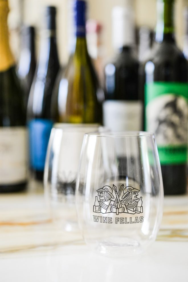 a wine fellas stemless wine glass with assorted natural wine bottles in the background