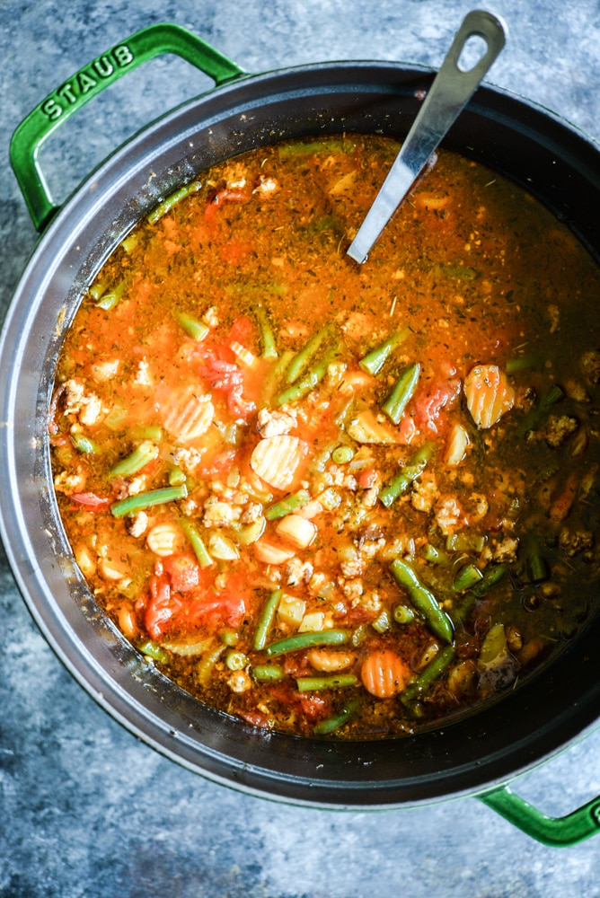 bright red paleo minestrone soup in a green cast iron pot on a dark grey board