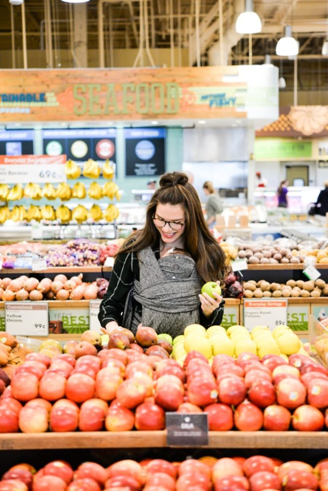 woman wearing a baby and grocery shopping