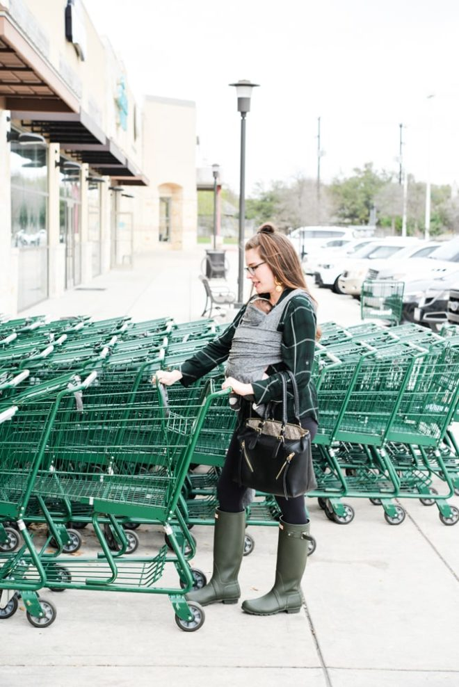 woman wearing a baby and grabbing a grocery cart