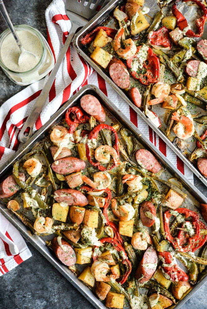 cajun sheet pan dinner with shrimp, sausage, bell peppers, red potatoes, and okra with a creamy remoulade sauce drizzled on top