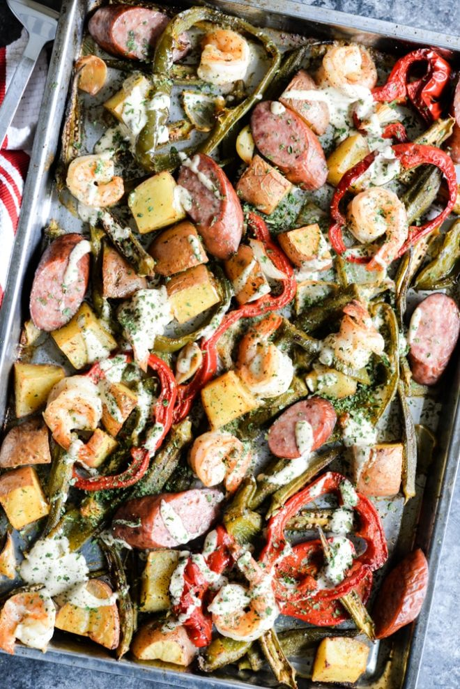overhead view of a sheet pan loaded with sausage, shrimp, potatoes, asparagus, and red bell peppers with a creamy sauce drizzled over it