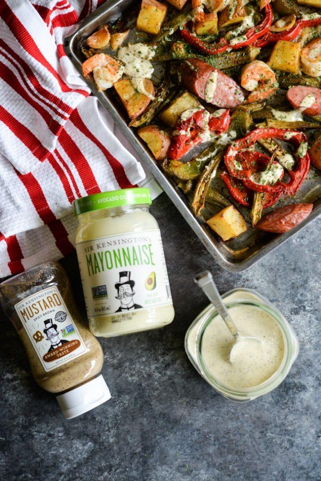 overhead view of cajun shrimp sheet pan dinner, sir kensingtons mustard and mayonnaise, and cajun remoulade sauce