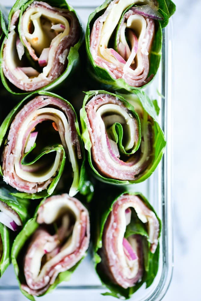 close up shot of collard green wraps filled with meat and cheese in a glass container on a marble surface