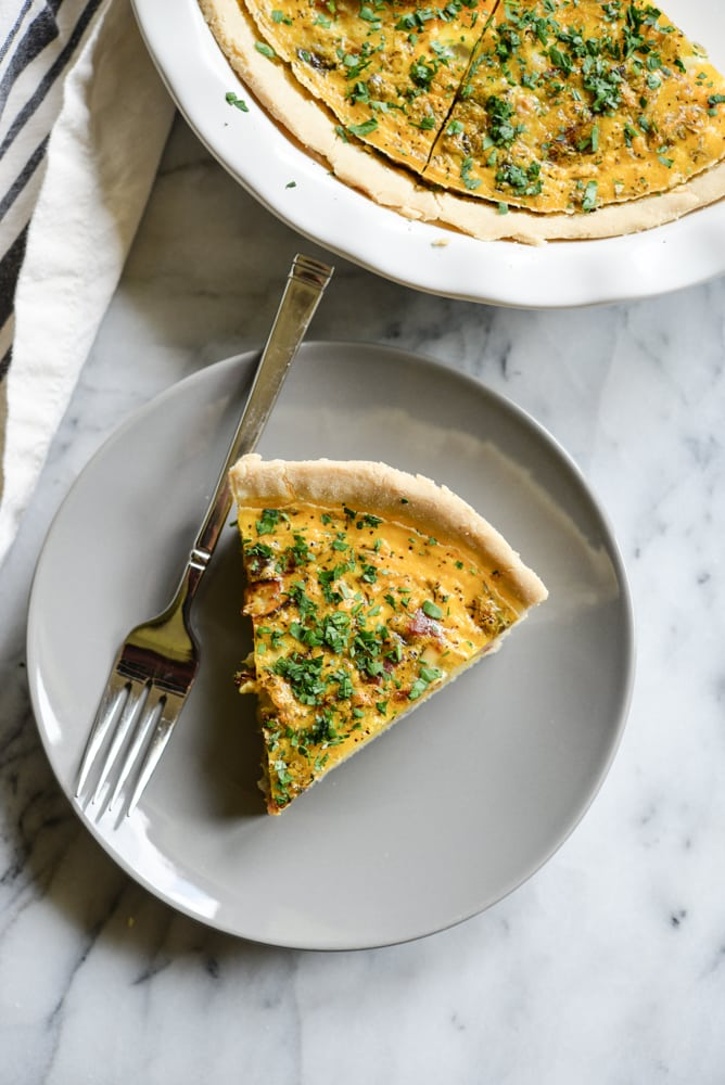 a slice of gluten-free quiche on a grey plate with a silver fork on a marble surface
