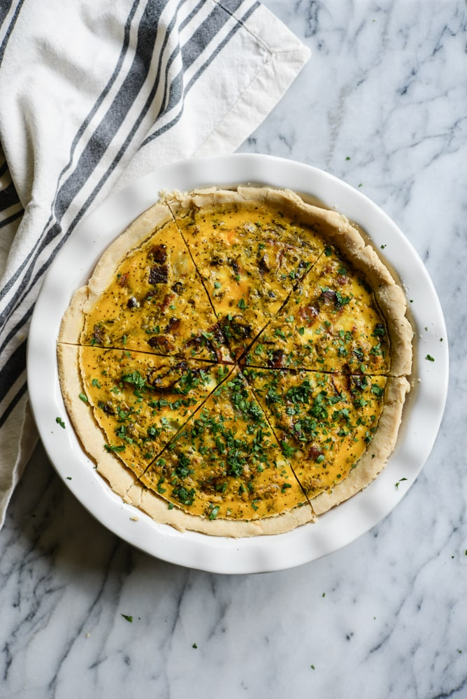 gluten-free quiche in a white pie dish on a marble surface