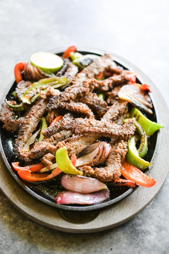 plate of sizzling beef fajitas with grilled red and green bell peppers and red onions