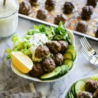 greek meatballs with tzatziki in a white bowl on a marble surface