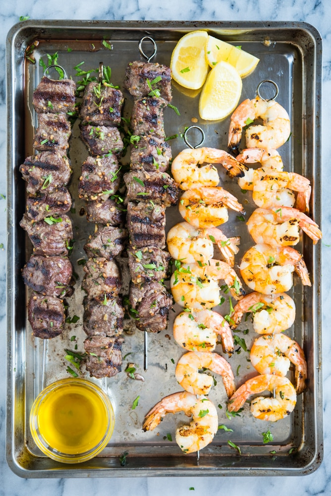 skewers of grilled beef and grilled shrimp on a sheet pan with a bowl of melted butter